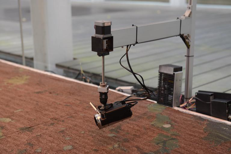 Camera attached to a robotic arm. It captures video footage as it slowly pans across the carpet, incorporating the carpet as landscape, just like the ruins.